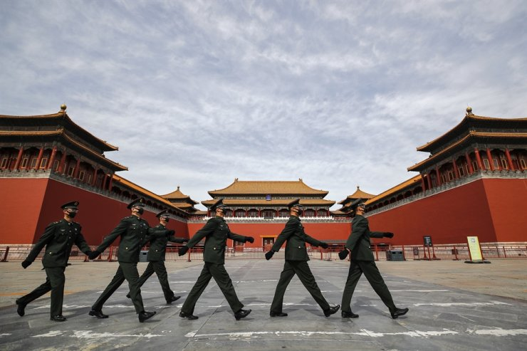 Soldiers wearing protective face masks march past the closed entrance gates to the Forbidden City, usually crowded with tourists before the new coronavirus outbreak in Beijing, Thursday, March 12, 2020. AP