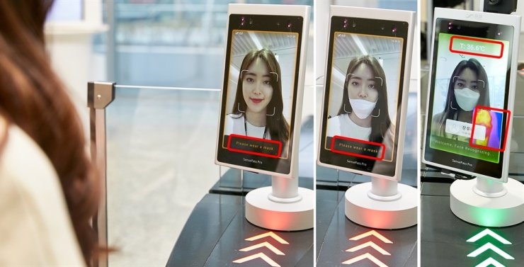 An LG CNS employee tests out the firm's newly implemented AI-based access control system, which is designed to prevent the entry of people who aren't wearing facial masks amid the COVID-19 outbreak, at its headquarters in western Seoul, Thursday. The system is also capable of checking temperatures. / Courtesy of LG CNS