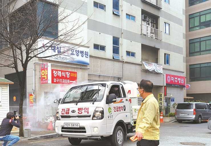 Quarantine officials spray disinfectant on a car in front of a hospital in Daegu, Friday, as a new cluster of COVID-19 infections emerged there. Yonhap