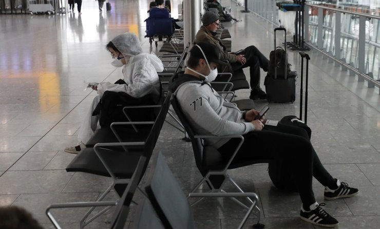 Travellers wear face masks as they wait at Heathrow Airport in London on Wednesday, March 18. AP
