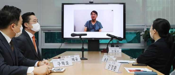 At a teleconference, Ahn Cheol-soo, on the monitor, speaks to his followers at People's Party headquarters in Seoul, Monday morning. Yonhap