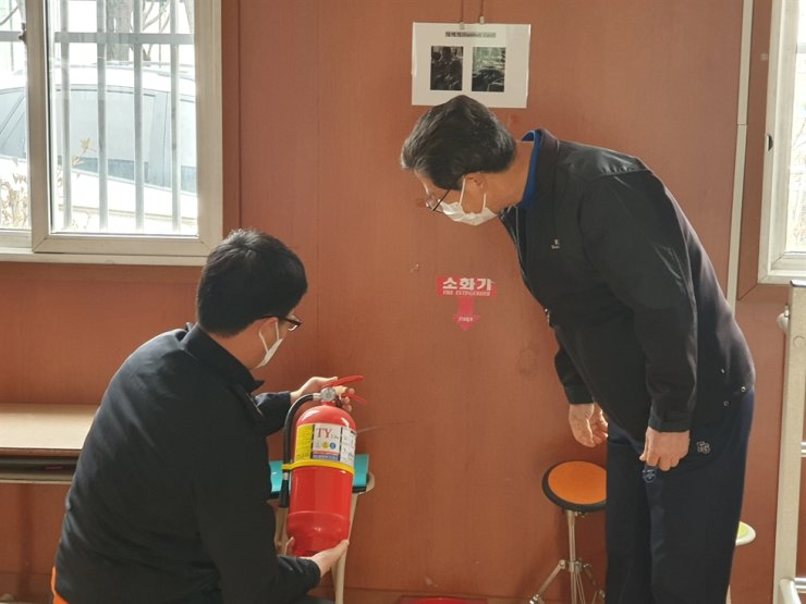 Rescue authority officers check on safety facilities at a polling station in Gwangju, Monday. Yonhap