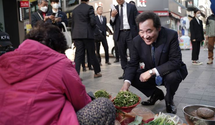 Lee Nak-yon, DPK candidate for Jongno, talks with a vendor at a market in Icheon, Gyeonggi Province, March 24. Yonhap