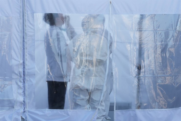Medical staff in full-protection gear take a sample for coronavirus testing at a hospital where confirmed cases occurred among patients and staff near Seoul. Korea Times