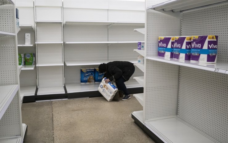 Deanna Butts reaches for one of the last packages of toilet paper at Target in the Tenleytown area of Washington, Tuesday. AP-Yonhap