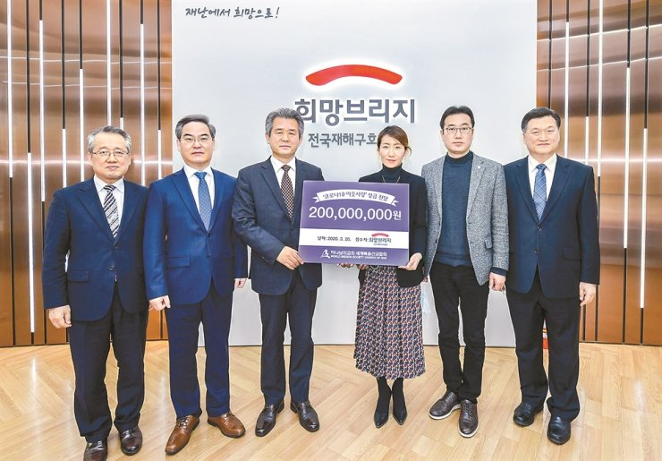 Church of God Pastor Kim Jung-rak, third from left, and Jeong Seo-yun, fourth from left, director of the fundraising headquarters of the Hope Bridge Korea Disaster Relief Association in Seoul, pose after the World Mission Society Church of God donated 200 million won ($160,000) to help COVID-19 patients, healthcare workers and volunteers fight the pandemic. / Courtesy of Church of God
