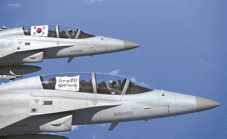 Republic of Korea Air Force pilots flying FA-50 fighters in a patrol over the East Sea, Monday, display the Taegeukgi national flag and a placard that reads