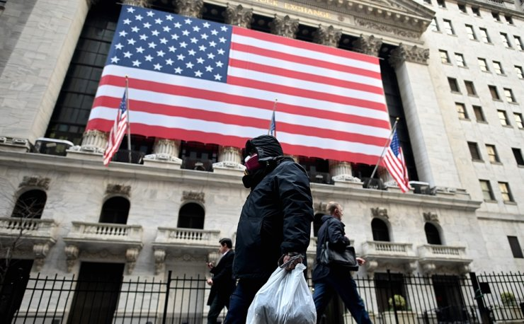 A man wearing a mask walks by the New York Stock Exchange (NYSE) on March 17, 2020 at Wall Street in New York City. (Photo by Johannes EISELE / AFP)