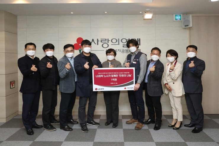 LG Chem employees pose with an official from the Community Chest of Korea after delivering a donation of 100 million won ($81,230), Tuesday. The company said its employees made a donation of 10,000 won each in a bid to help medical staff for the recovery of coronavirus patients and virus-hit small business owners. / Courtesy of LG Chem