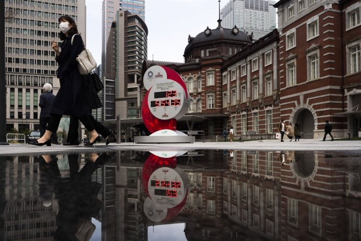 A countdown clock for the Tokyo 2020 Olympic Games is seen reflected in a puddle of water in front of Tokyo Station, March 23. / Yonhap