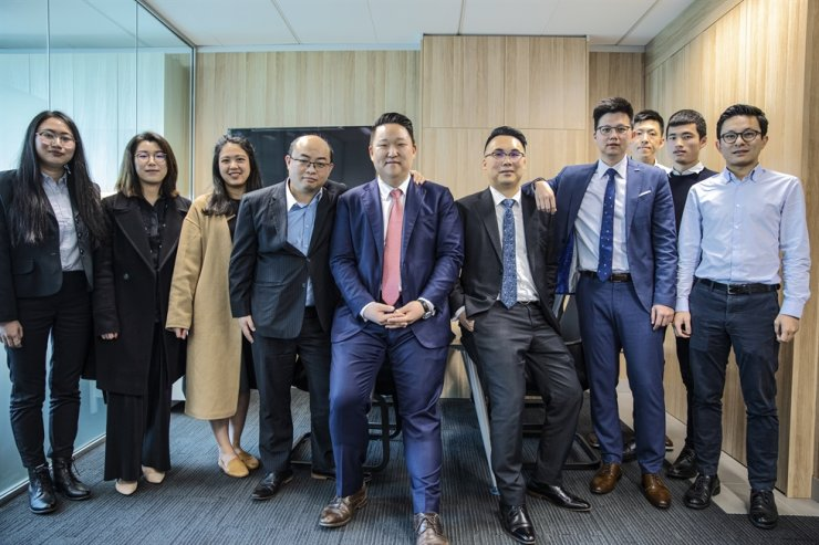 Solomons Group managing partner Johnny Shin, fifth from left, poses with his corporate advisory team members at the company's Sydney office in this 2019 file photo. / Courtesy of Solomons Group