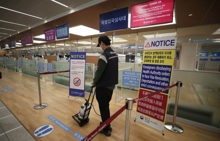 A health worker disinfects the immigration checkpoint at Incheon International Airport, Thursday. Korea Times photo by Shim Hyun-chul