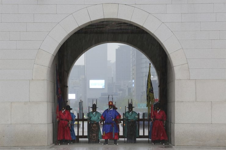 Imperial guards wearing face masks to help protect against the spread of the new coronavirus shelter from the rain under the gate of the Gwanghwamun at the Gyeongbok Palace in Seoul, Friday, April 17, 2020. AP