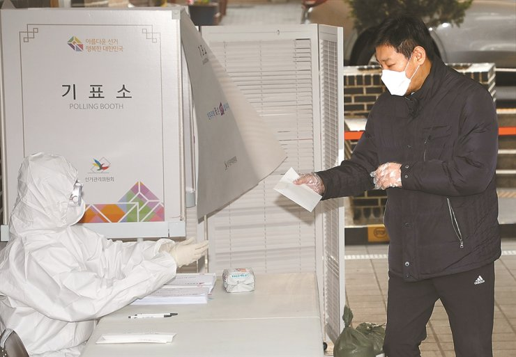 An election authority in protective clothing receives a self-quarantined voter at a polling station in Seoul, Wednesday. Voters ordered to isolate themselves to prevent COVID-19 infections were allowed to vote after regular voting ended at 6 p.m. / Yonhap