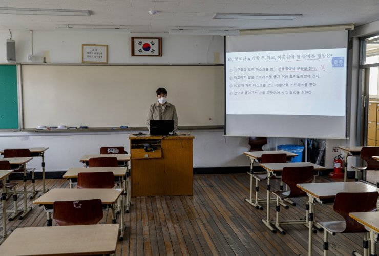 A teacher wearing a mask gives a lecture via online in an empty classroom at Seoul Girls High School in Seoul, Thursday, the first day of the new semester during the COVID-19 pandemic. In an unprecedented plan, middle schools and high schools in Korea have opened online as students stay home to avoid the coronavirus. Korea Times photo by Shim Hyun-chul