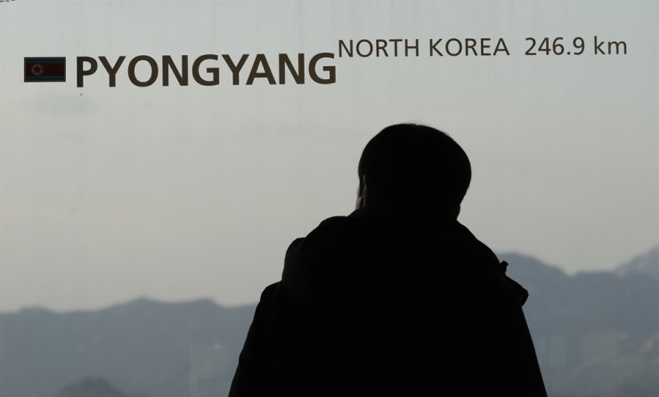 A visitor passes a window with a sign 'Pyongyang' at the N Seoul Tower in Seoul, South Korea, Sunday, April 26, 2020. A train likely belonging to North Korean leader Kim Jong Un has been parked at his compound on the country's east coast since last week, satellite imagery showed, amid speculation about his health that has been caused, in part, by a long period out of the public eye. (AP Photo/Lee Jin-man)