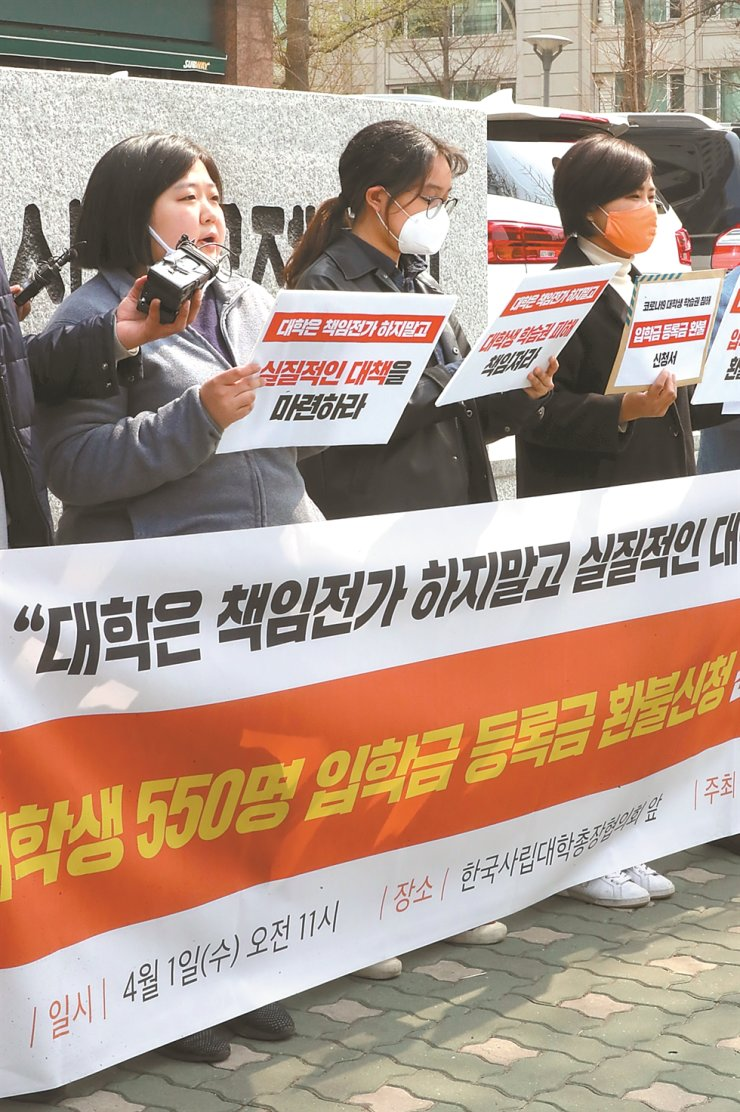 University students stage a protest in front of the Korean Association of Private University Presidents in Seoul, Wednesday, asking their tuitions to be reimbursed. Amid the new coronavirus outbreak, many universities shut their campuses down and offered online lectures but many students said they didn't like them.