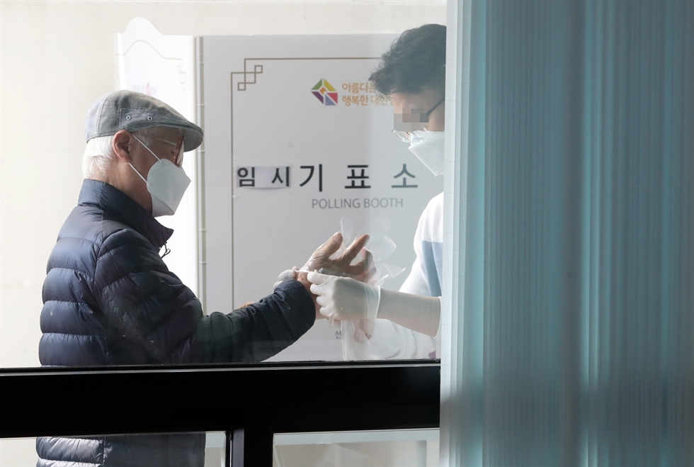 A woman in a face mask and disposable gloves ― preventive gear against the coronavirus spread ― casts her vote Wednesday at a polling station in Daejeon. Yonhap