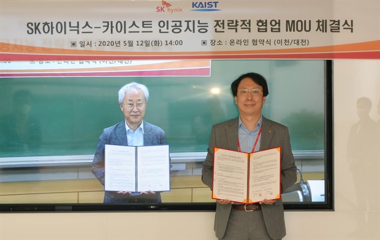 Song Chang-rock, right, leader of the data transformation division at SK hynix, poses with Park Hyun-wook, vice president for research at KAIST during a ceremony celebrating their online partnership, Tuesday. / Courtesy of SK hynix