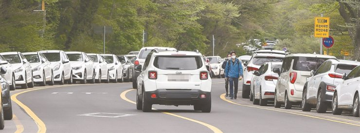 Vehicles were pulled over to the sides of the road near the Seongpanak Trail at Hallasan National Park on Jeju Island, Saturday. Since Thursday, the island has seen about 40,000 daily visitors. / Yonhap