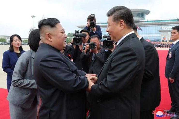 North Korean leader Kim Jong-un, left, and Chinese President Xi Jinping bid farewell at Pyongyang International Airport in Pyongyang after the latter's visit to North Korea in this June 2019 photo. / Korea Times file