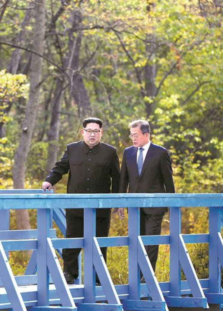 President Moon Jae-in and North Korean leader Kim Jong-un walk on a bridge in the truce village of Panmunjeom during their summit, April 27, 2018. / Korea Times