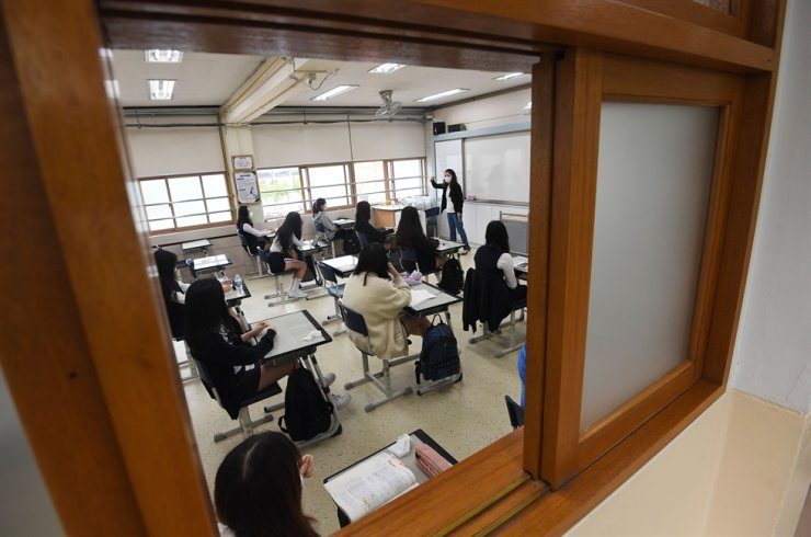 A class is under way with the teacher wearing a mask and students sitting relatively far from each other. Korea Times photo by Shim Hyun-chul
