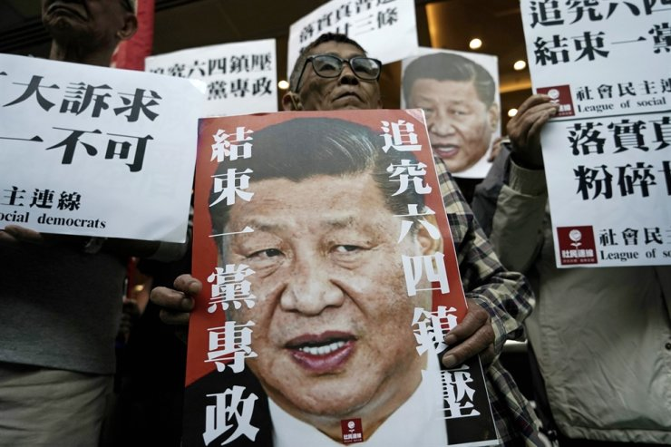 In this Wednesday, Dec. 18, 2019 file photo, pro-democracy activists hold up placards of Chinese President Xi Jinping with slogans including 'End one party state' at a ferry terminal in Hong Kong. China's ceremonial parliament will consider legislation that could limit opposition activity in Hong Kong, a spokesperson said Thursday, May 21, 2020. AP
