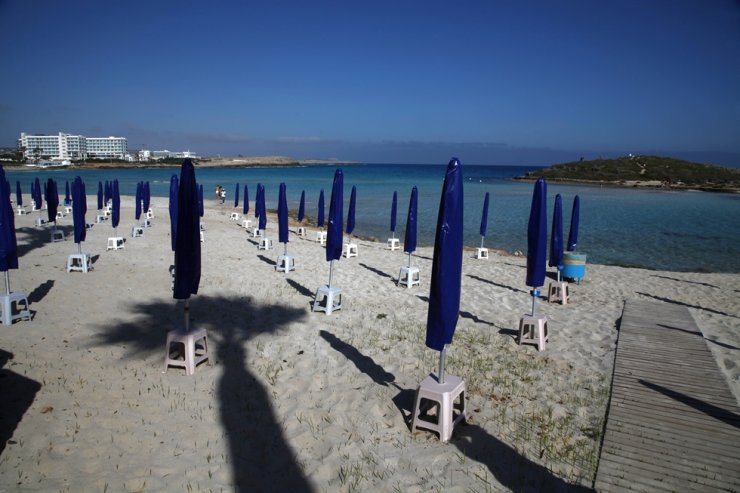 People walk among folded beach umbrellas dotted on an empty stretch of 'Nissi beach' in Ayia Napa, Cyprus, a seaside resort that's popular with tourists from Europe and beyond in this photo taken on May 10. /AP