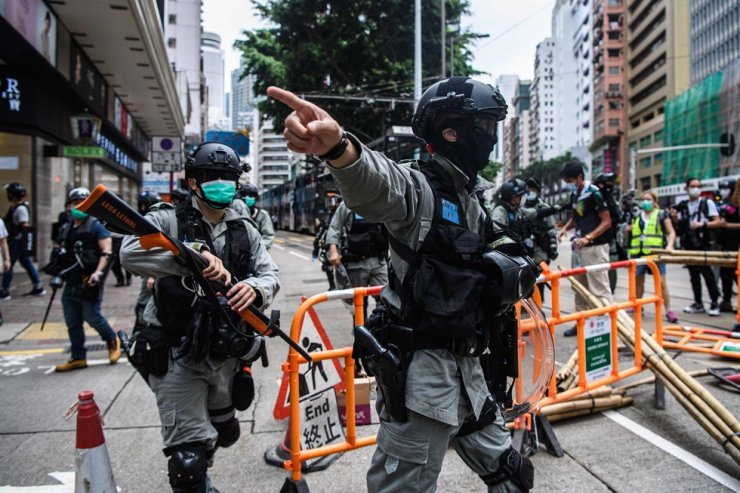 Riot police clear up debris left by protesters attending a pro-democracy rally against a proposed new security law in Hong Kong on May 24, 2020. AFP