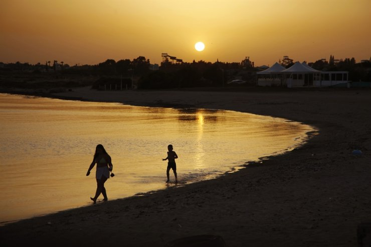Beachgoers walks at the sea water during sunset at an empty stretch of Dome beach hotel at Makrinissos in Cyprus' seaside resort of Ayia Napa, a favorite among tourists from Europe and beyond, on Sunday, May 17, 2020. With coronavirus restrictions gradually lifting, Cyprus authorities are mulling ways to get holidaymakers back to the tourism-reliant island nation. AP
