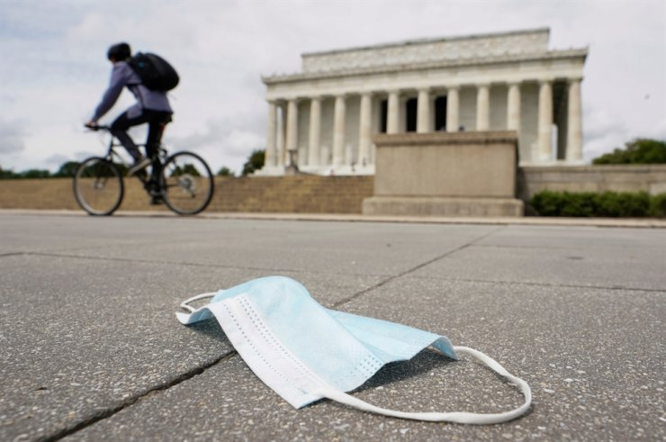 As the national death toll from the coronavirus disease (COVID-19) nears 100,000, a cyclist passes a discarded face mask in front of the Lincoln Memorial in Washington, U.S., May 27, 2020. /REUTERS