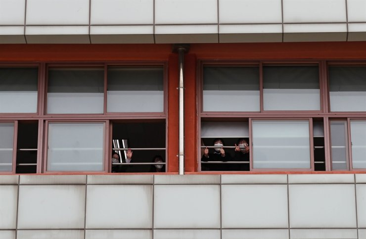 Mask-wearing students look out the windows of a high school in Seoul, Wednesday. Korea Times photo by Shim Hyun-chul