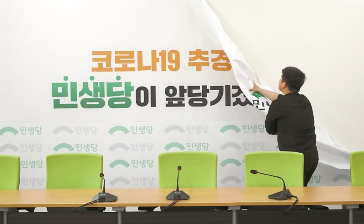 An official of the minor opposition Minsaeng Party removes a banner in the party's meeting room at the National Assembly in Seoul, Friday. In the April 15 general election, the party failed to win a single seat, so it is not permitted to have an office or a meeting room within the main Assembly building of the for the 21st Assembly that will start on May 30. In the 20th Assembly, the party had 20 lawmakers. Yonhap