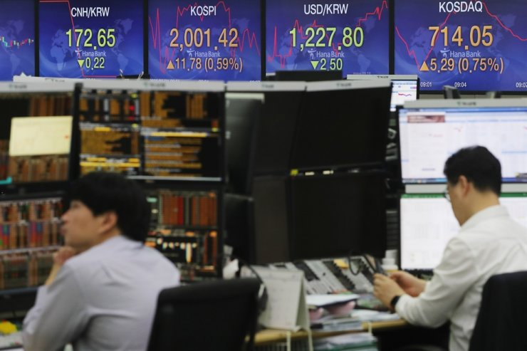 Dealers work at the headquarters of the KEB Hana Bank in central Seoul, Thursday, as the KOSPI started strong and exceeded the 2,000 mark for the first time since early March. / Yonhap
