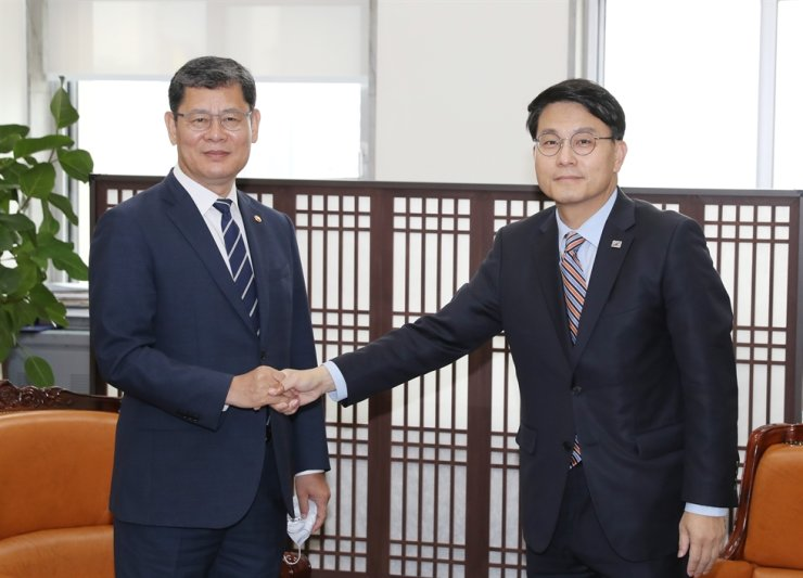 Rep. Yoon Sang-hyun, right, an independent lawmaker who heads the National Assembly's Foreign Affairs and Unification Committee, shakes hands with Unification Minister Kim Yeon-chul during their meeting at the Assembly in Seoul, Friday. / Yonhap