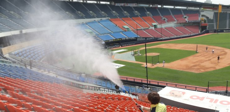 A health official sanitizes seats at Jamsil Stadium in Seoul, Monday, a day before the start of the 2020 Korea Baseball Organization season. The original opening day of March 28 was delayed due to the COVID-19 pandemic. Yonhap