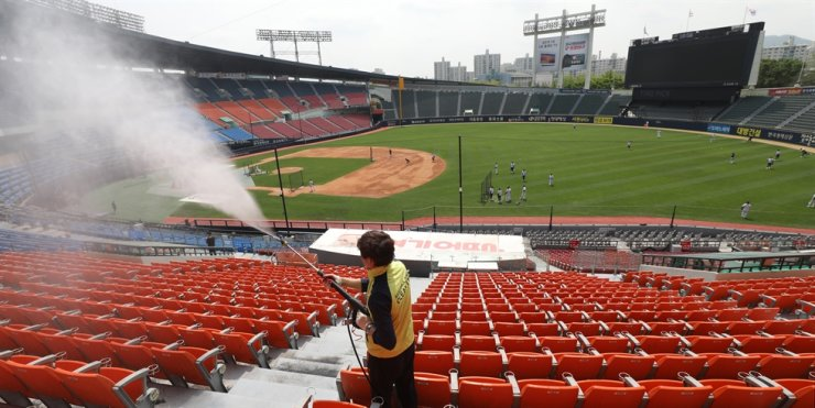 A health official sanitizes seats at Jamsil Stadium in Seoul, Monday, a day before the start of the 2020 Korea Baseball Organization season. Yonhap