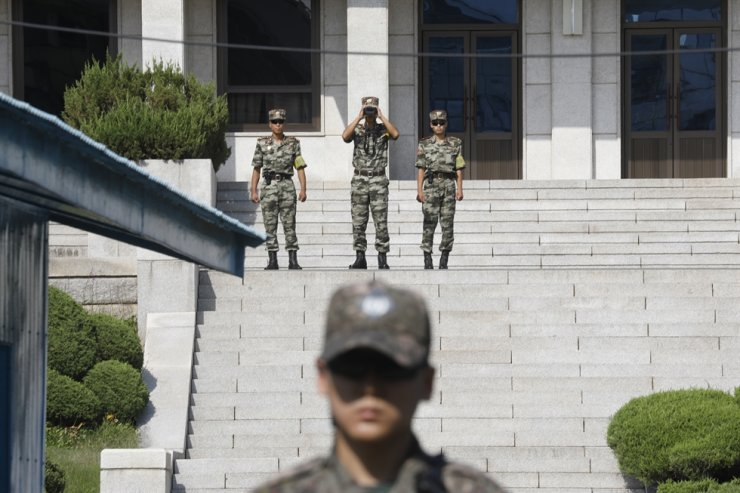 North Korean soldiers look toward the south as a South Korean soldier stands guard at the truce village of Panmunjom inside the demilitarized zone separating the two Koreas, South Korea, Wednesday, Aug. 28, 2019. AP