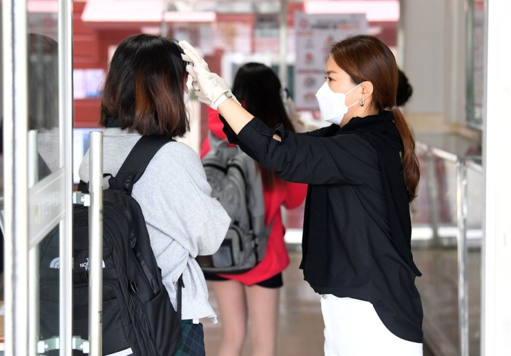 A teacher checks the temperature of a student at the main entrance, Wednesday. Korea Times photo by Shim Hyun-chul
