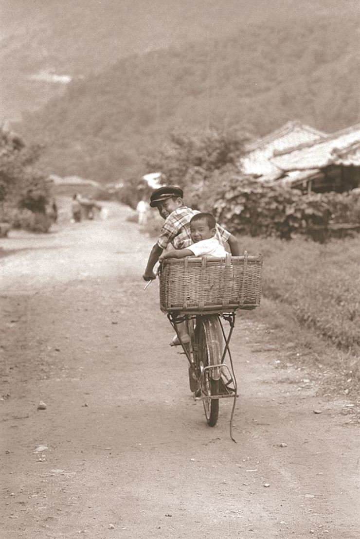Two boys on a bicycle look back as Rev. Nomura (not seen in this photo) takes a photo. / Photo from Noonbit Publishing