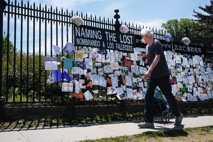 A man walks by a memorial for those who have died from the coronavirus outside Green-Wood Cemetery on May 27, 2020 in the Brooklyn borough of New York City. Green-Wood Cemetery, one of New York's oldest cemeteries, has been the site of hundreds of burials and cremations of Covid-19 victims. While certain neighborhoods are still seeing high infection numbers, New York has seen the number of deaths from COVID-19 statewide begin to consistently stay below 100 people per day. The United States has now surpassed 100,000 deaths from the virus. /AFP