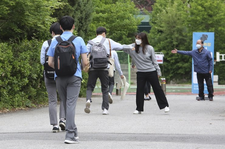 A senior student is greeted by a teacher, second from right, upon his arrival at the Kyungbock High School in Seoul, Wednesday, May 20, 2020. AP