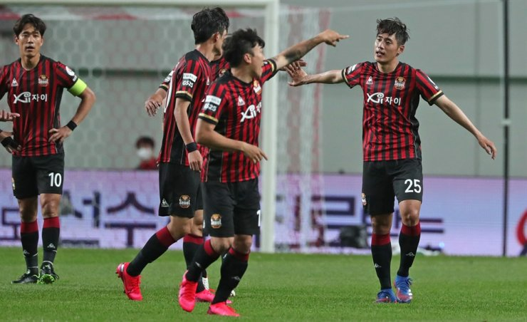 FC Seoul midfielder Han Chan-hee, right, celebrates with his teammates after scoring a winning goal during the K League 1 match against Gwangju FC at the Seoul World Cup Stadium, Sunday. / Yonhap