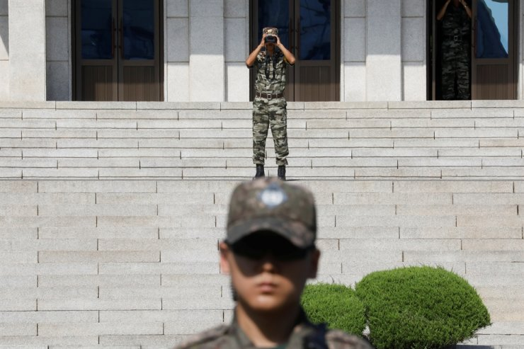 In this Aug. 28, 2019, file photo, a North Korean soldier looks toward the south as a South Korean soldier stands guard in the truce village of Panmunjom inside the demilitarized zone separating the two Koreas, South Korea. Reuters