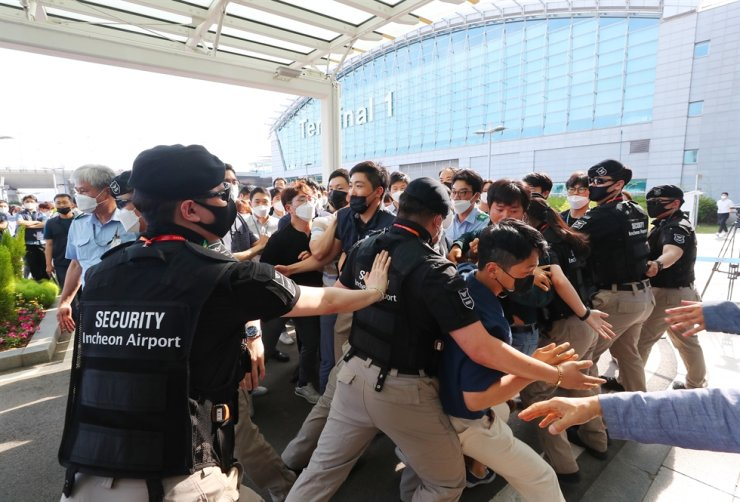 Full-time workers at Incheon International Airport Corp. protest the company's decision to grant regular employment status to to 1,902 current contract or part-time security officers working at the airport, Monday. / Yonhap