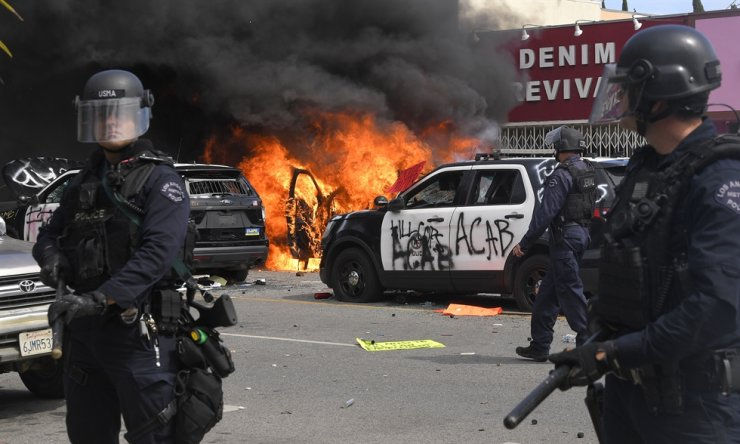 Los Angeles police officers watch a police car burn during a protest in Los Angeles, Saturday, May 30, 2020, Protests were held throughout the country over the death of George Floyd, a black man who died after Minneapolis police officers restrained him on May 25. AP