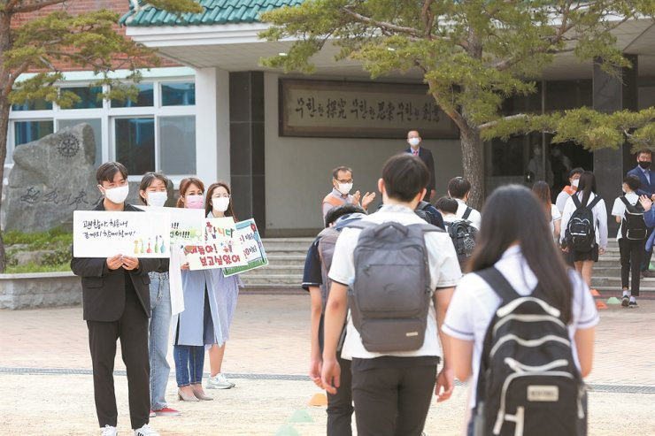 Teachers hold signs welcoming freshmen at Youngil High School in Pohang, North Gyeongsang Province, Wednesday. Some 1.78 million additional students nationwide, including high school freshmen, were allowed to physically attend classes after a 94-day delay due to the COVID-19 pandemic. / Yonhap