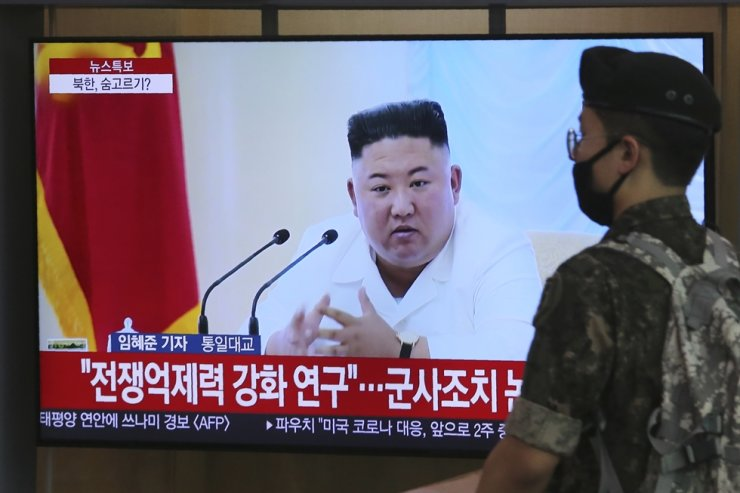An army soldier passes by a TV showing a file image of North Korean leader Kim Jong-un during a news program at the Seoul Station in Seoul, Wednesday. AP-Yonhap