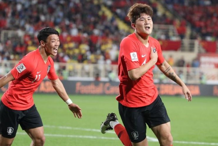 Kim Min-jae, right, celebrates after scoring a header during the Asian Cup qualification game against China at the Al Nahyan Stadium in Adu Dhabi, Jan. 16. 2019. / Yonhap